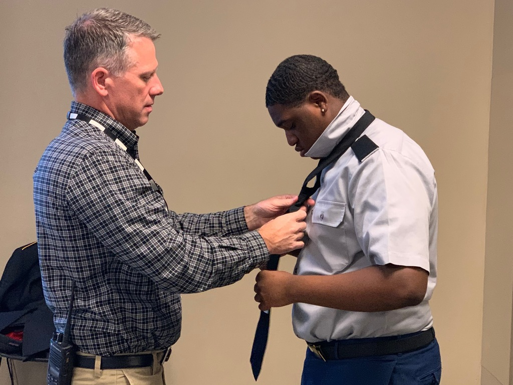 Jennings helping student with tie