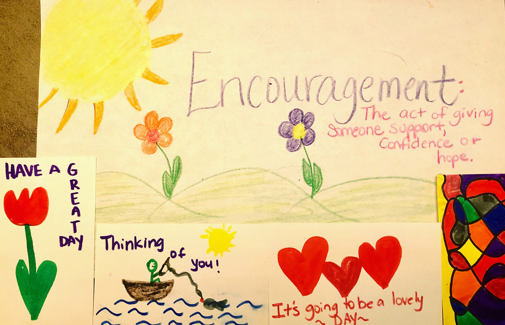 Homemade sign that reads ENCOURAGEMENT in purple  with several multicolored cards of encouragement